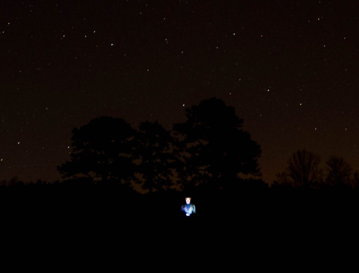 Photo of someone looking at their phone in the middle of the night outdoors