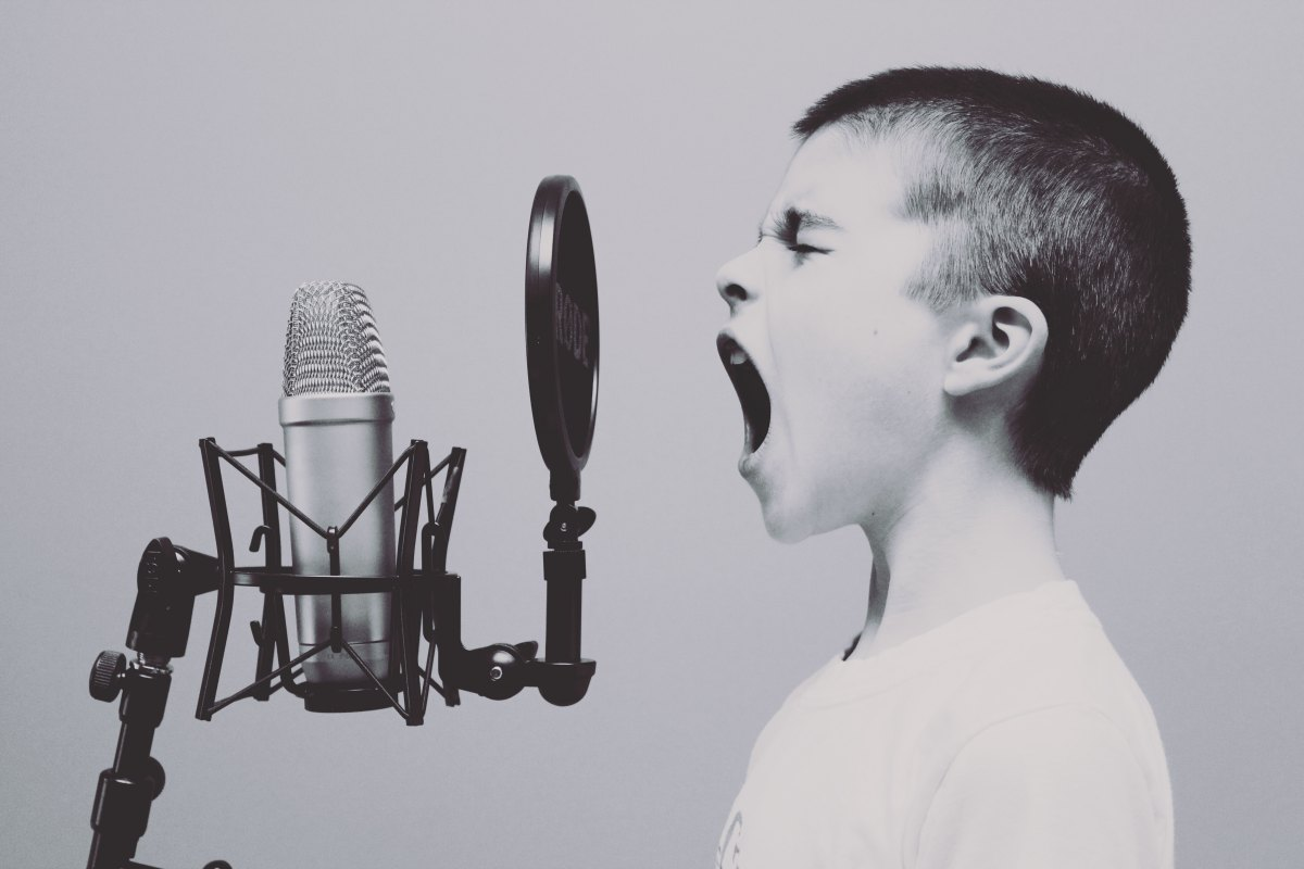 Photo of a kid shouting into a mic