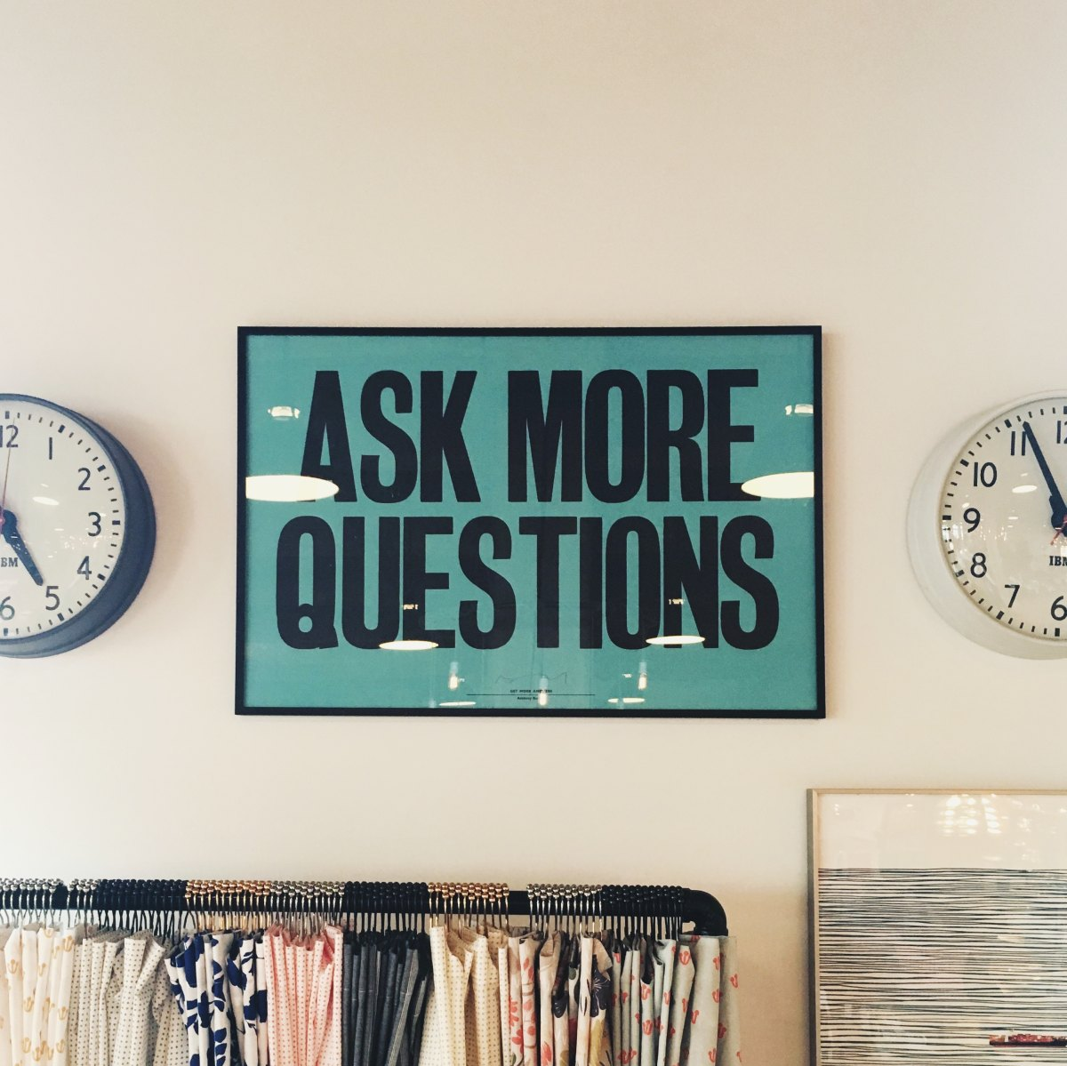 Photo of wall clocks and a poster that reads Ask More Questions